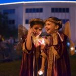Elle Perez, 6, left, laughs with Sara Christina De Roman, 6, while dressed as angels for The Nutcracker performace during the Tree Lighting Ceremony in Coral Gables at City Hall on 405 Biltmore Way on Friday, Dec. 7, 2012 in Miami, Fla.